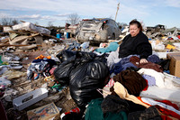 Chrys Michaels salvages what she can from the debris of homes where several people died in tornado destruction in East Bernstadt, Kentucky
