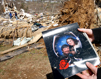 Charlotte Jones holds a photo of her sister Melissa Evans and Ricky Batey with the house Melissa died in, in the background near Crossville, TN